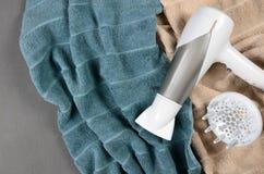 Hairdryer branco em toalhas bege e esverdeado-azuis Vista superior Fotos de Stock