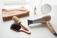 Hairdryer, cepillos de pelo, espejo y toalla imagenes de archivo