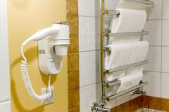 Hair dryer in a holder on hotel bath wall. royalty free stock photography