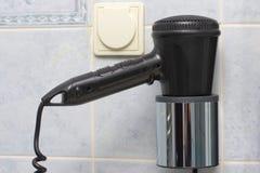 Hairdryer para la sequedad del pelo en la habitación en el cuarto de baño Imágenes de archivo libres de regalías