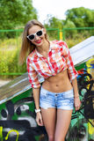 Haired beautiful girl with glasses, smiling outdoor young happy,  shirt, a bright sun in denim shorts, Royalty Free Stock Photography