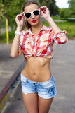 Haired beautiful girl with glasses, smiling outdoor young happy,  shirt, a bright sun in denim shorts, Stock Photos