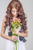 Haired girl in a wedding dress and makeup with a festive with a bouquet of roses Stock Photo