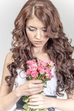 Haired girl in a wedding dress and makeup with a festive with a bouquet of roses Stock Photos