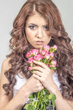 Haired girl in a wedding dress and makeup with a festive with a bouquet of roses Royalty Free Stock Images