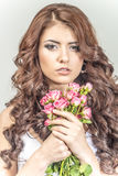 Haired girl in a wedding dress and makeup with a festive with a bouquet of roses Stock Image