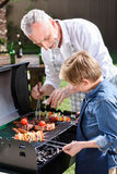 Haired grandfather with his grandson preparing meat and vegetables on grill outdoors. Grey haired grandfather with his grandson preparing meat and vegetables on Stock Images
