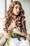 Haired meisje in een huwelijkskleding en make-up met feestelijk met een boeket van rozen stock foto