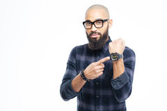 Hairless african man in glasses with beard pointing on watch Stock Photos