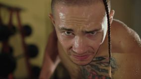 Hairless with tattoos free fighter lifts the dumbbells in front of camera. 4K. Close-up of hairless with tattoos free fighter lifts the dumbbells in front of stock video footage