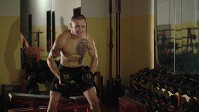 Hairless with tattoos free fighter lifts the dumbbells at mirror. 4K.  stock footage