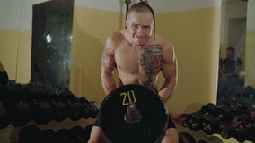 Hairless with tattoos free fighter lifts the hard barbells in gym. 4K.  stock video