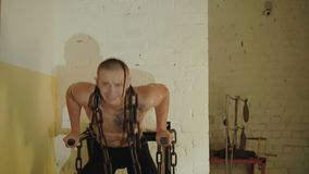 Hairless with tattoos free fighter pushing with hard chains on a neck in gym. 4K.  stock video