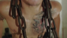 Hairless with tattoos free fighter pushing with hard chains on a neck in gym. 4K.  stock video footage