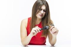 Hairloss и вопросы плешивости Молодая кавказская женщина имея проблемы волос Проверка волос в щетке для волос платье представляя  стоковое изображение