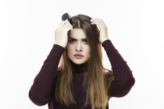 Hairloss and Baldness Issues. Young Caucasian Female Having Hair Problems. Checking Hair in Hairbrush. Against White. Horizontal Image Orientation royalty free stock images