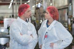 Hairnet команды биолога говоря и нося в фабрике Стоковая Фотография RF