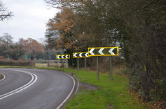 Hairpin bend. Sharp left hand bend on a rural road in Sussex,England.Large chevron road signs warn traffic users of danger royalty free stock photography