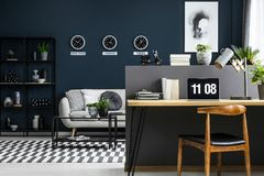 Hairpin desk with books, laptop and lamp in dark industrial living room interior with decor on metal rack, carpet and three clock. S on the wall stock photo