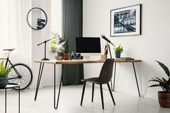 Hairpin desk with mockup monitor, plants and telescope standing. In bright room interior with poster on the wall and window with drapes stock photo