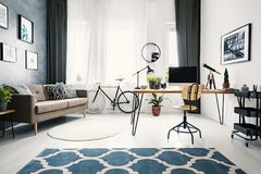 Hairpin table with retro telescope, computer, plants and lamp st. Anding in modern living room interior with two carpets, windows with curtains, bicycle and royalty free stock photography