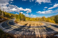 Hairpin turn at autumn in Colorado, USA. Highway with hairpin turn switchback at autumn sunny day in Rocky Mountain National Park. Colorado, USA stock photos