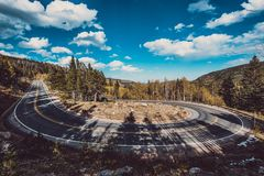 Hairpin turn at autumn in Colorado, USA. Highway with hairpin turn switchback at autumn sunny day in Rocky Mountain National Park. Colorado, USA royalty free stock photography