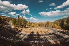 Hairpin turn at autumn in Colorado, USA. Highway with hairpin turn switchback at autumn sunny day in Rocky Mountain National Park. Colorado, USA stock photography