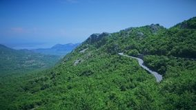 Aerial view of a curved winding road with cars passing. Mountain road. Hairpin turn in the forest. Aerial view of a curved winding mountain road with cars stock footage