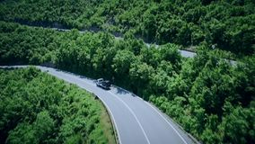 Aerial view of a curved winding road with cars passing. Mountain road. Hairpin turn in the forest. Aerial view of a curved winding mountain road with cars stock video footage