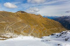 Hairpin turns of mountain pass Stelvio Pass named Stilfser Joc. H in Deutsch, in Italy during Autumn royalty free stock images