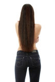 Hairs. Back of young woman with long hairs dressed in jeans royalty free stock image
