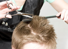Hairstyle. Hairdresser cuts client with scissors royalty free stock photo