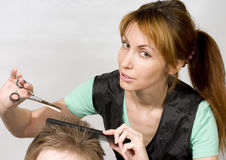 Hairstyle. Pretty woman hairdresser cuts client royalty free stock images