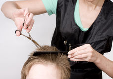 Hairstyle. Hairdresser cuts client with scissors royalty free stock images