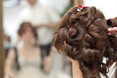 Hairstyle brunette. Women in front of mirror Royalty Free Stock Image
