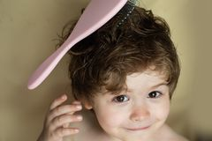 Hairstyle for a child. Baby with a comb. Stylish boy. Combing hair. Barbershop. Beauty saloon. Cute kid with wet hair royalty free stock photography