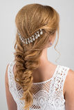 Hairstyle. Collected in a braid blonde hair with a beautiful decoration. Photo from the back on a light background Royalty Free Stock Image