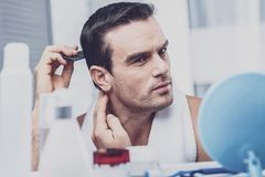 Concentrated model styling his hair. Hairstyle. Concentrated handsome model standing in front of the shelf with cosmetic products and styling his hair with a Stock Image