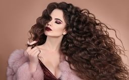 Hairstyle. Fashion brunette girl with Long curly hair, beauty ma. Keup. Glamour portrait of beautiful brunette with marsala matte lips in pink fur coat isolated royalty free stock photo