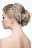 Hairstyle with hair accessory. Portrait of attractive young woman with beautiful hairstyle and stylish hair accessory, side view Royalty Free Stock Image