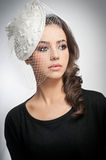 Hairstyle and make up - beautiful young girl art portrait. Cute brunette with white cap and veil, studio shot. Attractive female. With beautiful lips and eyes Royalty Free Stock Photo