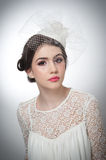 Hairstyle and make up - beautiful young girl art portrait. Cute brunette with white cap and veil, studio shot. Attractive girl Stock Photography