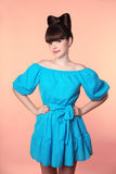 hairstyle Menina de sorriso bonita com o cabelo da curva que levanta em d azul Fotografia de Stock