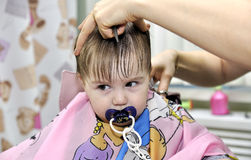 Hairstyle of the one year old child first time. Hairstyle of the one-year-old child first time Royalty Free Stock Image