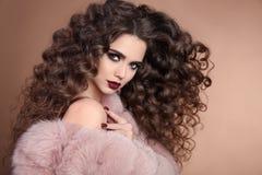 hairstyle Pelo de la belleza Muchacha morena de la moda con la ha rizada larga fotografía de archivo