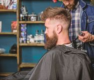 Hairstyle service concept. Hipster bearded client got hairstyle. Barber with trimmer or clipper shaved neck of client. Barber with clipper works on hairstyle stock photo
