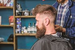 Hairstyle service concept. Hipster bearded client got hairstyle. Barber with clipper works on hairstyle for bearded man. Barbershop background. Barber with royalty free stock images