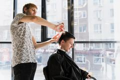 Hairstyling del ` s de los hombres y el haircutting en un salón de la peluquería de caballeros o de pelo fotos de archivo