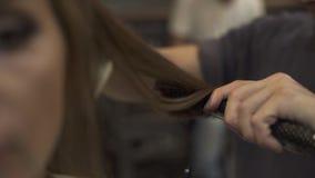 Hairstyling della donna con il ferro dei capelli nella fine del salone di lavoro di parrucchiere su Hairstyling facendo uso delle archivi video